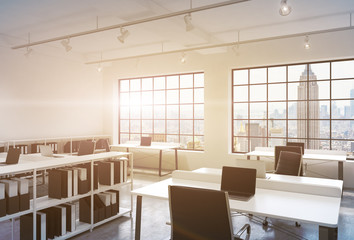 Workplaces in a bright modern loft open space office. Tables equipped with laptops; corporate documents' shelves. New York in the panoramic windows. 3D rendering. Toned image.