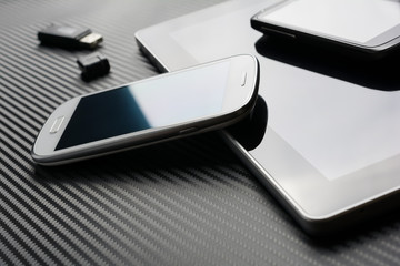Blank Phones With Reflection Lying And Leaning On Business Tablet Beside An USB Flash Drive Above A Carbon Background