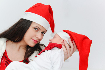 Happy mother with male baby wearing christmas hats