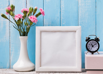 Blank white frame, pink flowers and alarm clock
