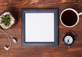 Blank frame, cup of coffee, alarm clock and succulent plant on t