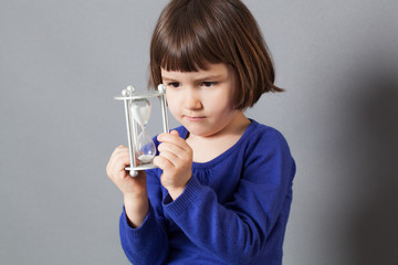 kid time concept - serious female preschooler enjoying learning about time, holding an hour glass for insouciance and future,studio shot