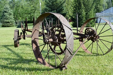 Vintage rusty farm equipment on display in an open space park