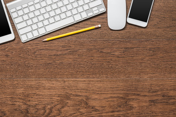 office wooden table with yellow pencil, tablet, keyboard, mouse
