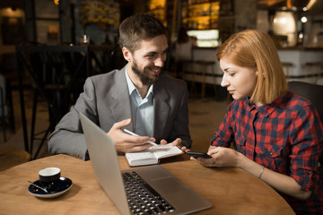 Business meeting of man director and woman worker in cafe