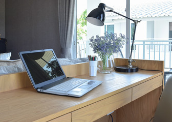 wooden table with computer notebook,pencil,lamp and artificial f