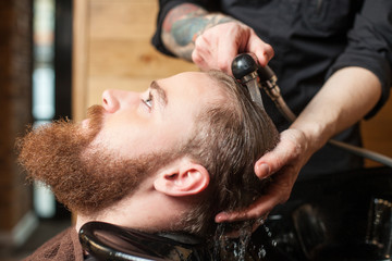 Professional male hairdresser is cleaning human head