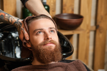Cheerful guy with beard at beauty salon