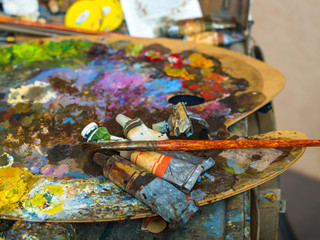 Tubes of paint on a palette for mixing oil paints. Creative mess. The color palette close up.