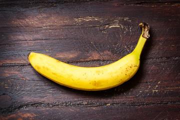 Banana on dark ol wooden table
