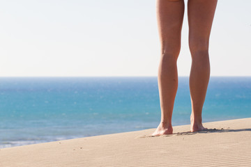 Women's legs from behind. Recreation. Blue sea