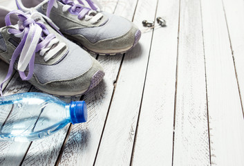 Pair of sport shoes, water bottle and earphones on white wooden