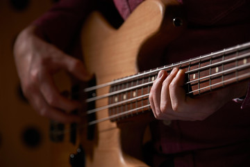 Close Up Of Bass Guitarist Playing Instrument