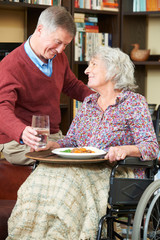 Senior Man Serving Wife In Wheelchair With Meal