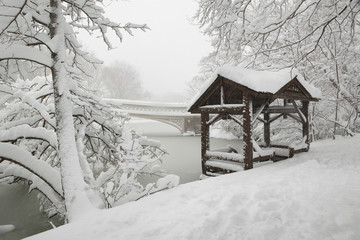 Central Park peaceful winter scene after heavy snowfall. The Bow Bridge and a wooden gazebo are covered by fresh snow at The Lake. Manhattan, New York City