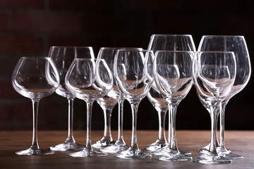 Empty wine glasses on a table on a brick wall background
