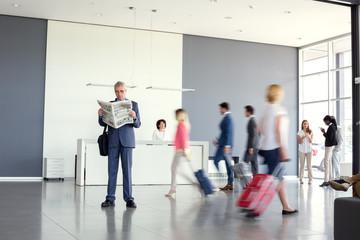 Businessman read newspaper while wait airplane