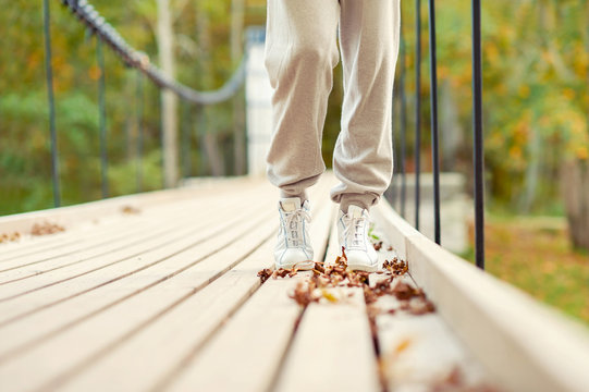 Woman feet in white shoes walking in autumn park