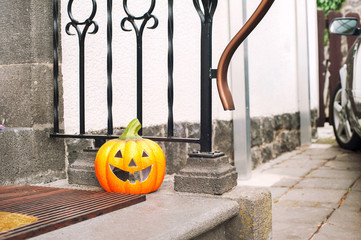 Smiling halloween Pumpkin near the door. Horizontal outdoors ima