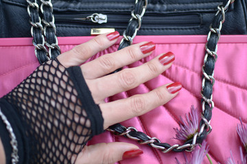fingers with burgundy lacquer,palm to webbed glove on a black and pink  purse with a chain and zipper