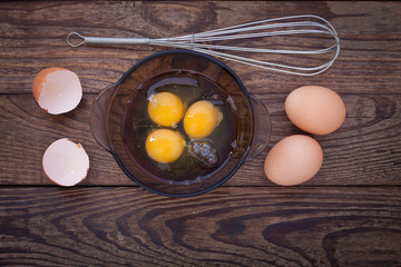 Raw eggs in bowl for whipping on wooden. Baking ingredients.