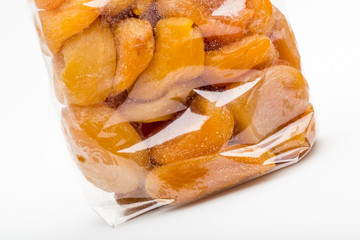 Closeup on candied apricots stacked into transparent plastic bag