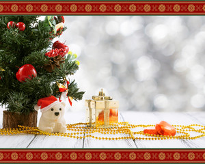 Greeting card with Christmas tree, gold gift box, balls, toy bear, candies and decorations on retro vintage white table isolated on white with red and golden ornament on blurred background
