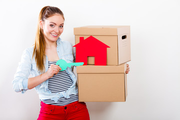 Woman moving in with boxes and paper house key.