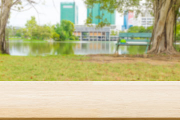 Wood table top in lawn with blurred lake and city background : Suitable use for montage or display your product.