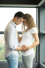Happy and young pregnant couple in studio, white background