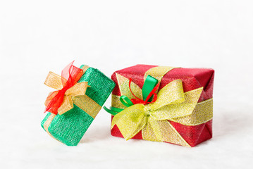 Red and green Christmas gift box with shiny golden ribbon on white background.