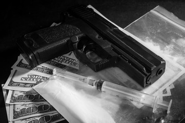 Syringe and gun on drug bag with money.