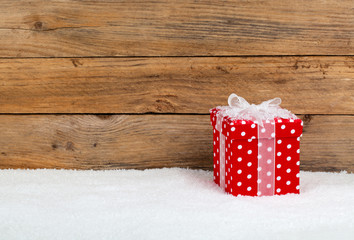 christmas red gift with snow, on wooden background