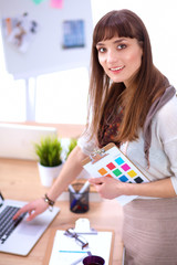 Young attractive fashion designer standing by desk in office, holding folders