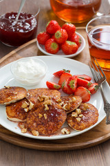 Pancakes with fresh strawberries and cream, jam and tea