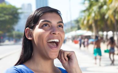 Gut gelaunte Brasilianerin mit langen Haaren in der Stadt