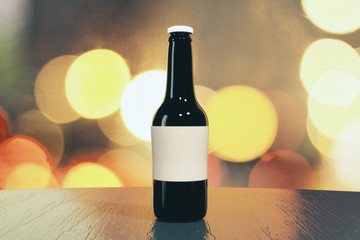 Black beer bottle with blank sticker on wooden table, mock up