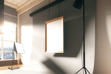 Blank picture frame in empty photo studio with equipment and whi