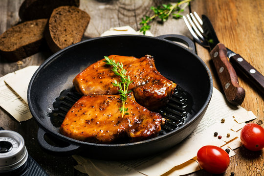 BBQ pork chops in sweet honey and pepper glaze on iron skillet, close up
