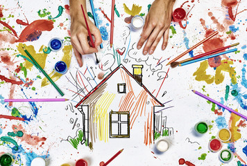 Hands draw house