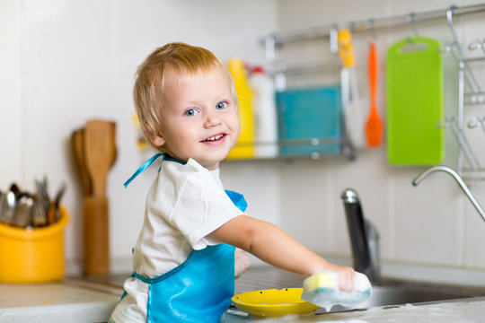 Toddler child washing dishes in kitchen. Little boy having fun with helping to his mother with housework