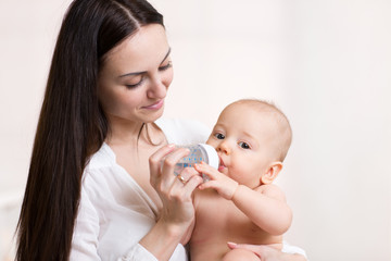 happy mother feeds her baby bottle
