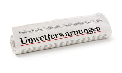 Zeitungsrolle mit der Überschrift Unwetterwarnungen