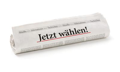 Zeitungsrolle mit der Überschrift Jetzt wählen