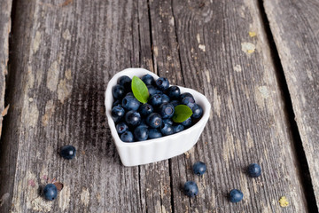 Heart shaped bowl of blueberries on wooden table