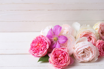 Sweet pastel roses and clematis flower on white  wooden backgrou