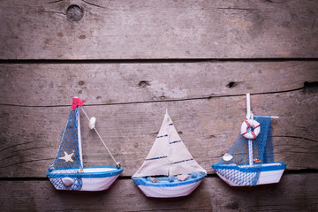 Decorative sailing boats on  vintage wooden background.