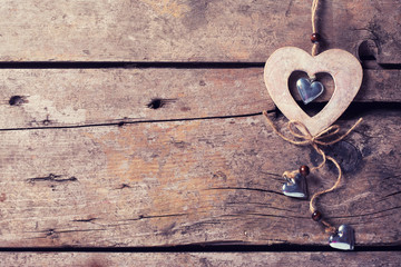 Rustic decorative heart on aged wooden  background.