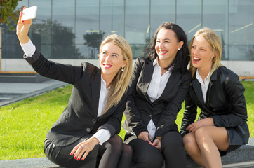 Three business women smiling and taking picture of themselves