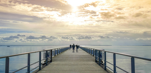 Long pier over the sea shore with sihouette of walkers